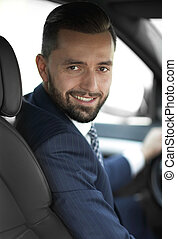 Handsome young man sitting in the front seat of a car looking at the camera