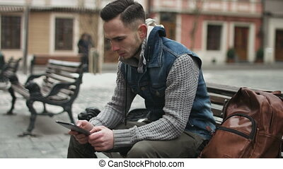Handsome young man sitting on a bench in the center of european city using a tablet. Guy playing online games on his mobile device.