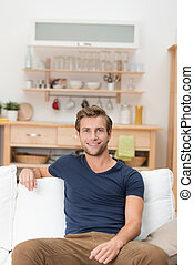 Handsome young man sitting on a sofa