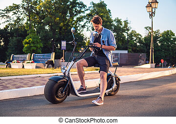 Handsome young man sitting on electric bike or scooter