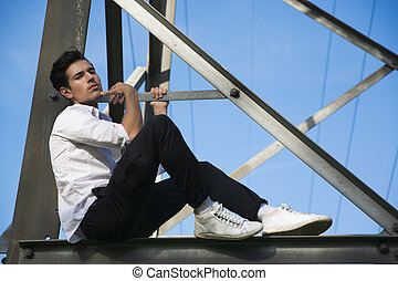 Handsome young man sitting on metal electricity trellis