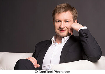 Handsome young man sitting on sofa. Happy young businessman on dark background