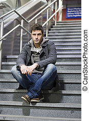 Handsome young man sitting on stairs