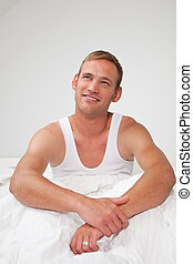 Handsome young man sitting thinking in bed
