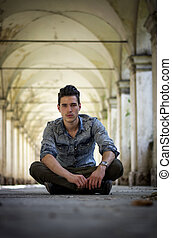 Handsome young man sitting under old colonnade