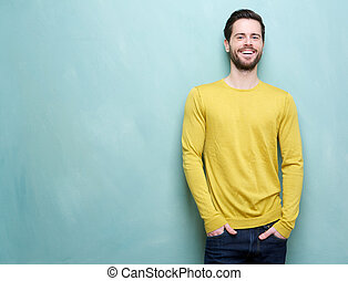 Handsome young man smiling against blue background