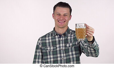 Handsome young man smiling joyfully, holding out his beer to the camera