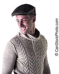Handsome young man smiling, wearing knitted wool white sweater and leather hat
