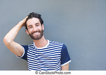 Handsome young man smiling with hand in hair