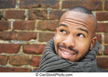 Handsome young man smiling with scarf outdoors