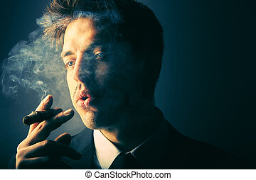 Handsome young man smoking cigar