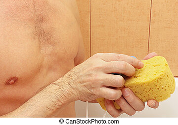 Handsome young man soaping yellow sponge with soap