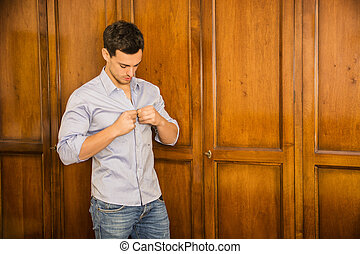 Handsome young man standing against wardrobe