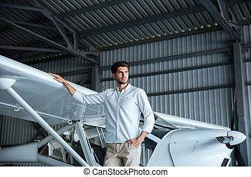 Handsome young man standing near smal airplane