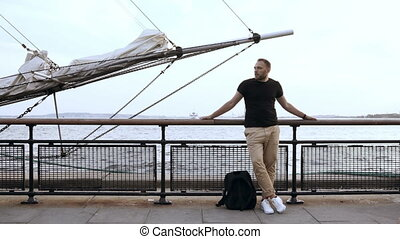 Handsome young man standing on the pier, near the fence close to the bowsprit of the ship and looking around.