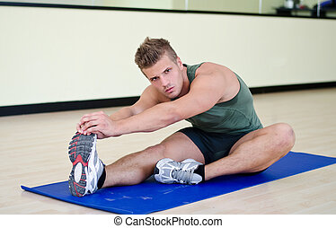 Handsome young man stretching on gym mat