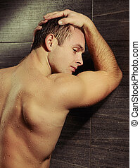 Handsome young man taking a shower - Manly and muscular....