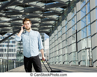 Handsome young man talking on mobile phone at airport with bags