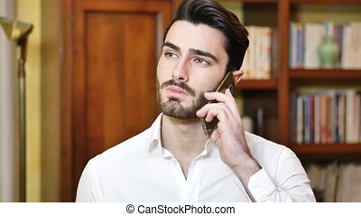 Handsome young man talking on telephone at home