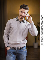 Handsome young man talking on the phone at home