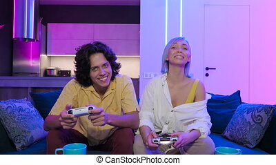 Handsome young man teaching how to play the video games to his girlfriend, on the couch, concept about home entertainment, video games.
