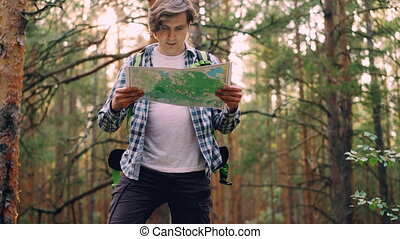 Handsome young man traveler is walking in forest then...