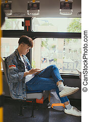Handsome young man traveling by bus and using a digital tablet