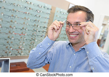 handsome young man trying pair of glasses