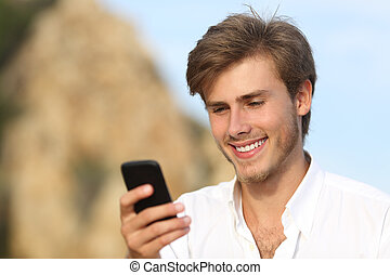 Handsome young man using a mobile phone outdoor