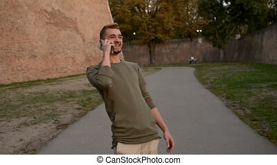 Handsome young man using his phone outdoors - Young hipster...