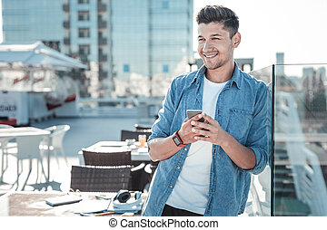 Handsome young man using smartphone on terrace