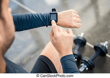 Handsome young man using smartwatch at gym