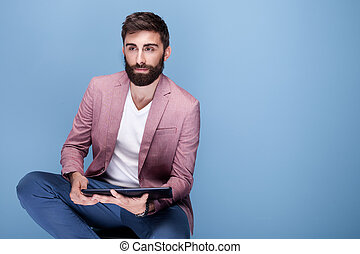 Handsome young man using tablet.