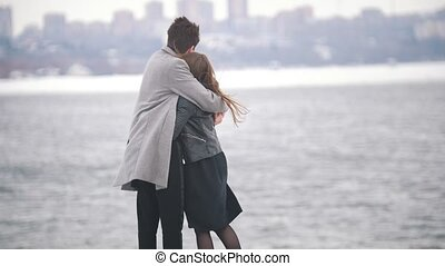 Handsome young man warms the girl with his coat on the bridge on a windy day