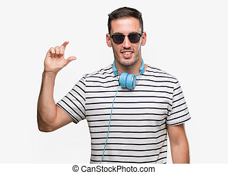 Handsome young man wearing headphones smiling and confident gesturing with hand doing size sign with fingers while looking and the camera. Measure concept.