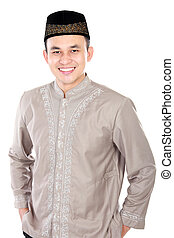 handsome young man wearing muslim dress posing on white...
