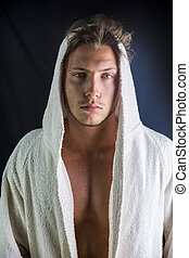 Handsome young man wearing white bathrobe