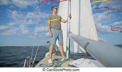 Handsome young man, who is the captait of this yacht, pulling on rope to sail out in the sea in summertime