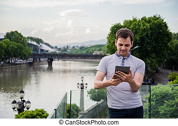 Handsome young man with a tablet in his hands standing and smiling near the river at european city