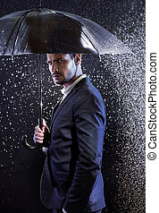 Handsome young man with an umbrella