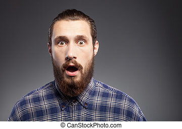 Handsome young man with beard is showing surprise