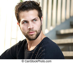 Close up portrait of a handsome young man with beard looking away