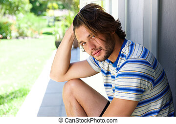 Handsome young man with beard sitting outside