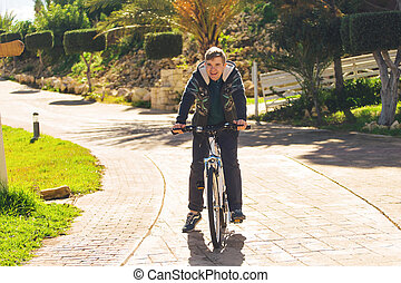 Handsome young man with bicycle in park on sunny day