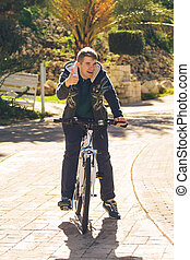 Handsome young man with bicycle showing thumbs up in park on sunny day