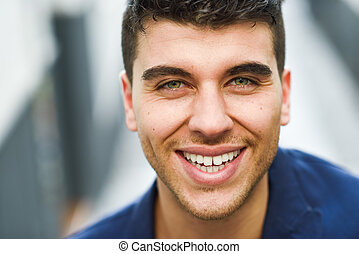 Handsome young man with blue eyes posing near a wall - Good...