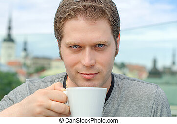 Handsome young man with cup of coffee