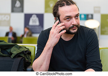 Handsome young man with dreadlocks using his phone at an airport lounge.