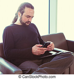 Handsome young man with dreadlocks using his phone at an airport lounge with backlight.