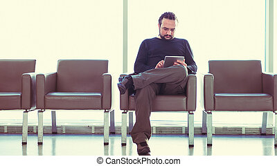 Handsome young man with dreadlocks using his digital tablet pc at an airport lounge, modern waiting room, with backlight.